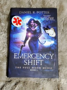 Emergency Shift book pictured with two badges